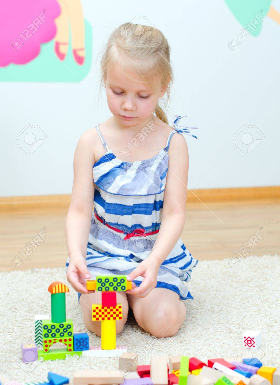 Cute little girl sitting on the floor and playing with building blocks Stock Photo - 18523846