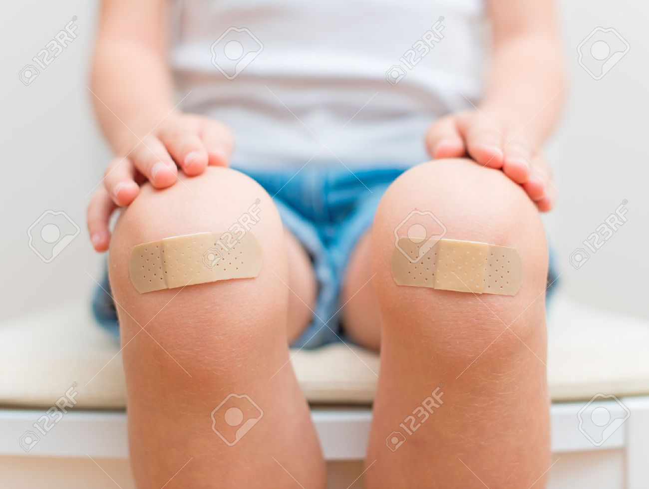Child knee with an adhesive bandage - 30980610