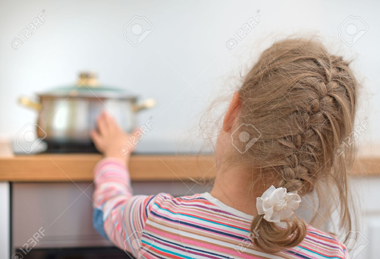 Little Girl Touches Hot Pan On The Stove. Dangerous Situation At Home