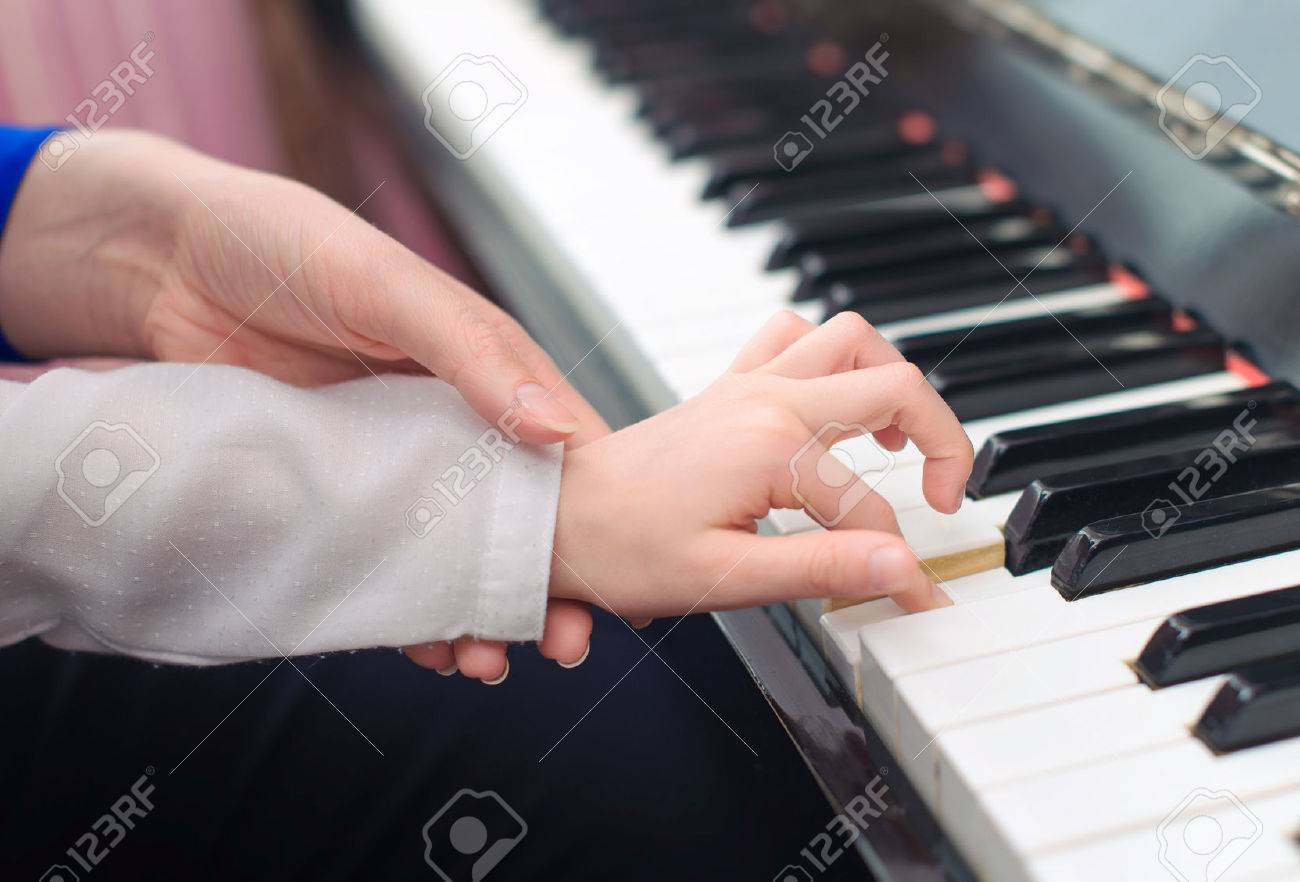 Woman teaching little girl to play the piano. - 40220292
