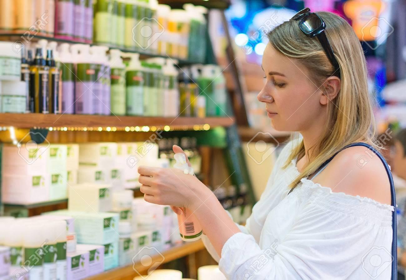 Young woman choosing cosmetic cream in beauty shop. - 46204785