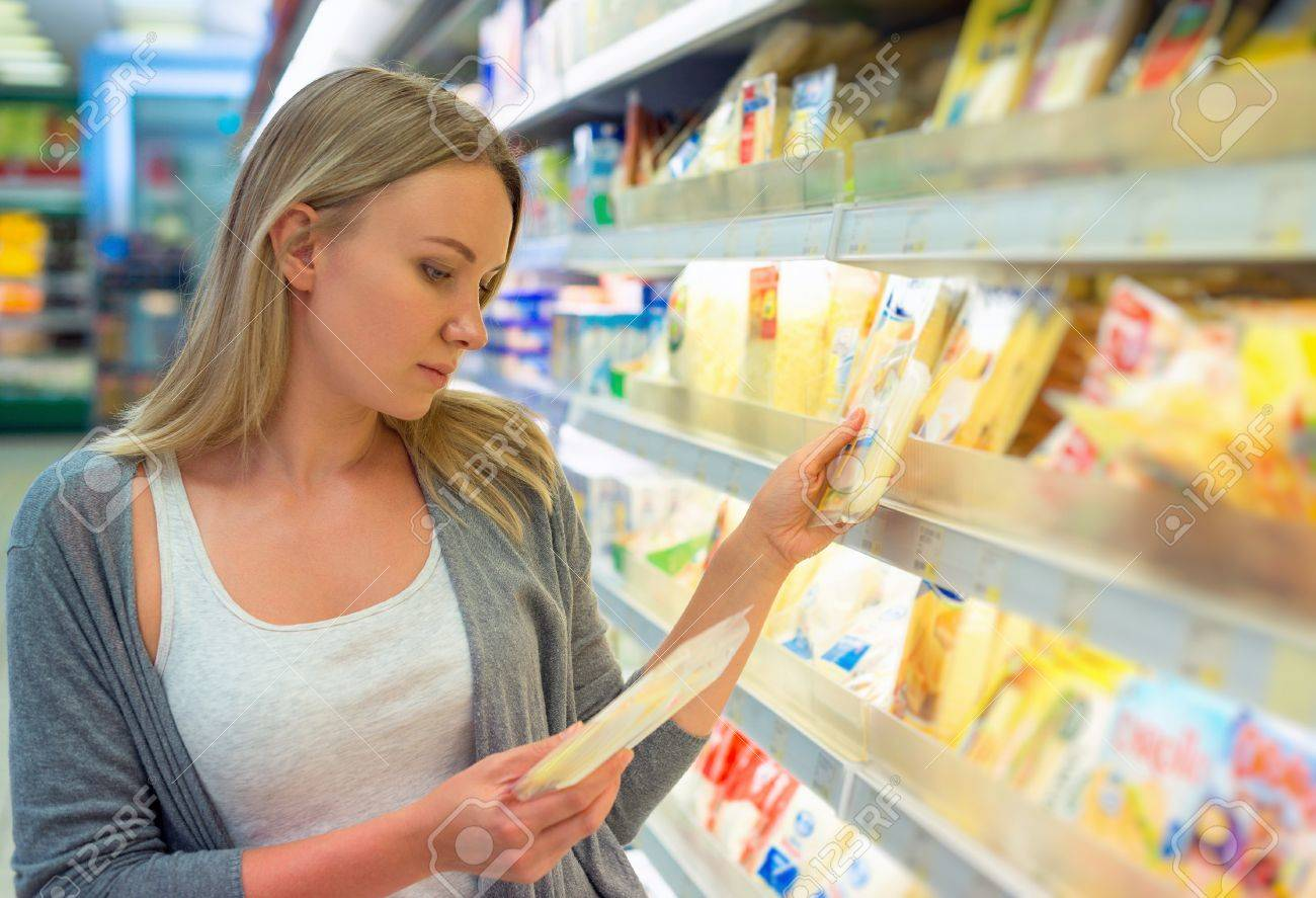 Woman choosing cheese in grocery store. - 48955327