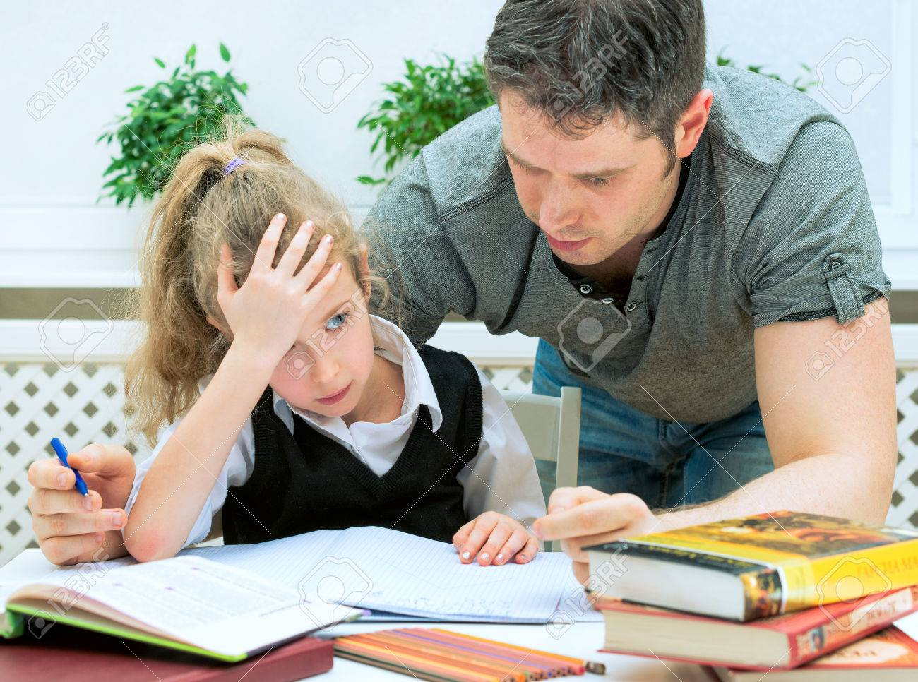 Father helping daughter with homework at home. - 50737058