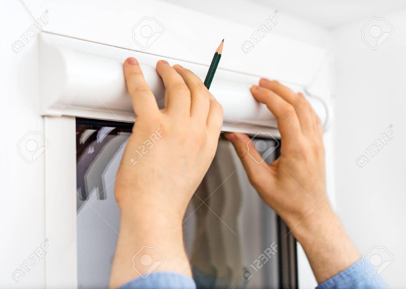 Man installing cassette roller blinds on windows. - 65136121