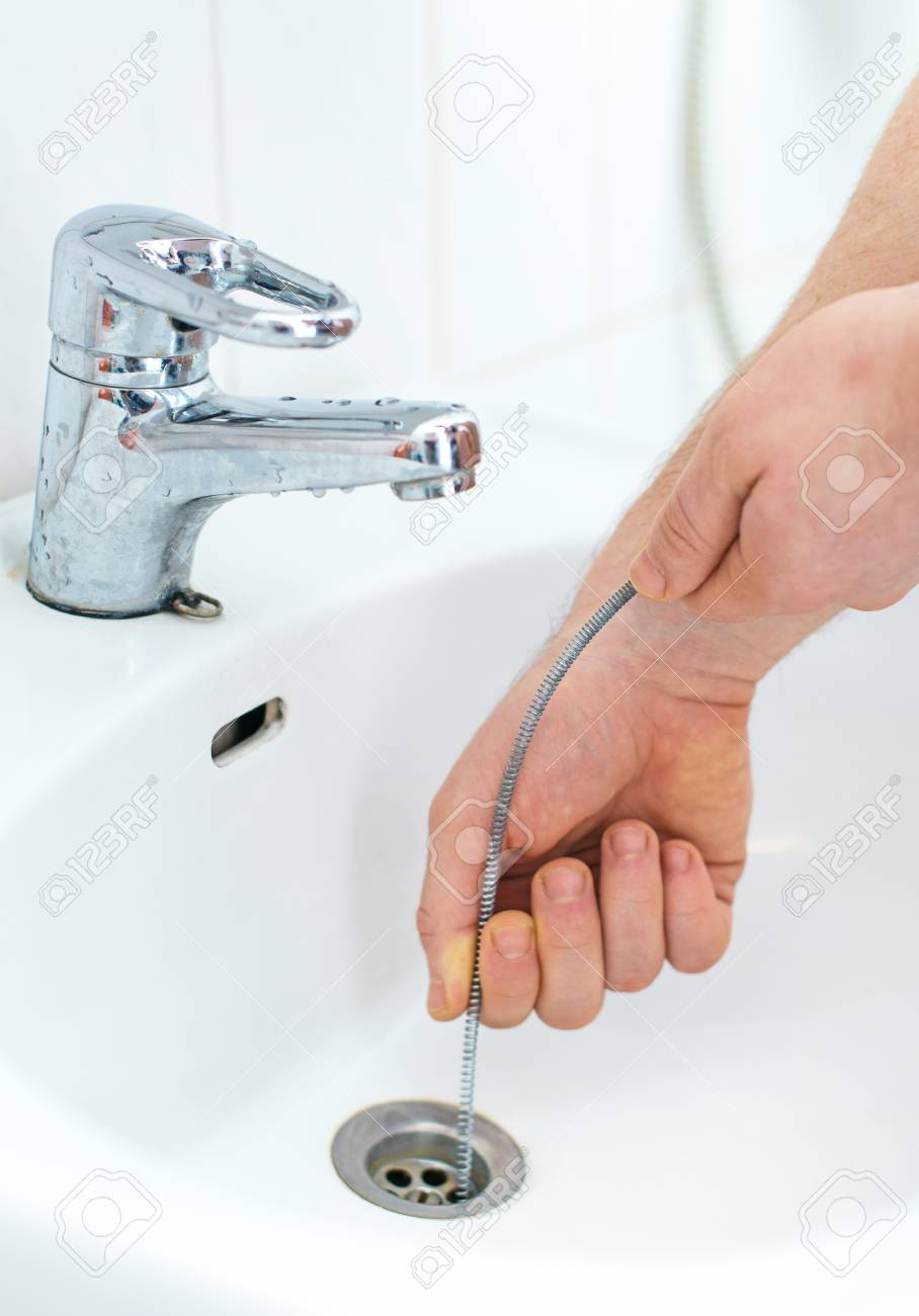 Plumber repairing sink with plumber's snake. - 70948856