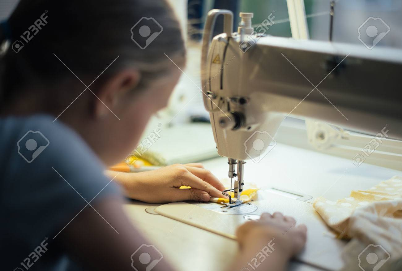 Little girl working on sewing machine at home. Close-up view. - 85134640