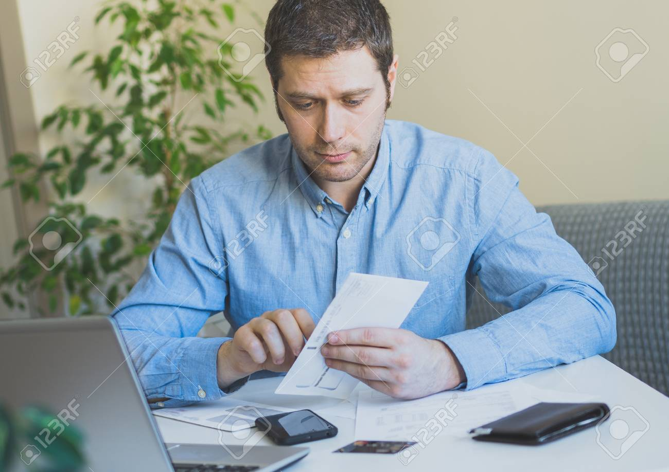 Handsome man opening his monthly bills at home. - 99364824