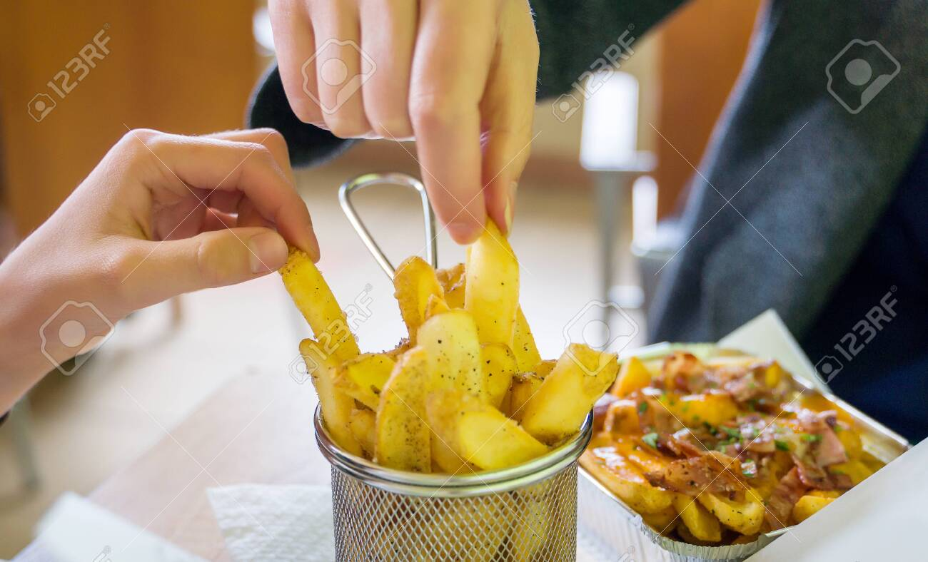 Fast food. Family eating french fries in restaurant. - 129929565