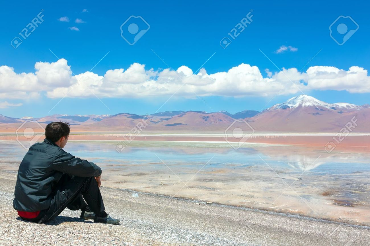 young man sitting alone on the shore of laguna colorada bolivia