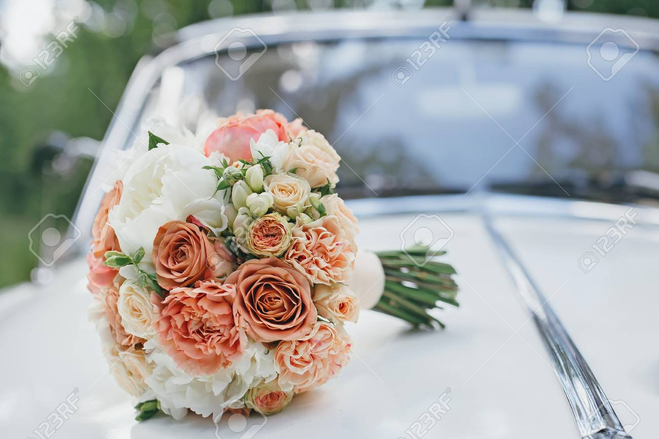 Wedding bouquet on the hood of a white retro car - 66577987