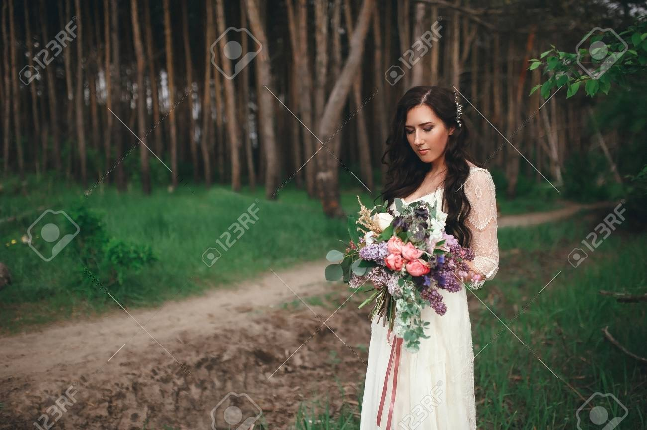 Beautiful Bride In The Forest With A Large Bouquet Of Different Stock Photo Picture And Royalty Free Image Image 71018387