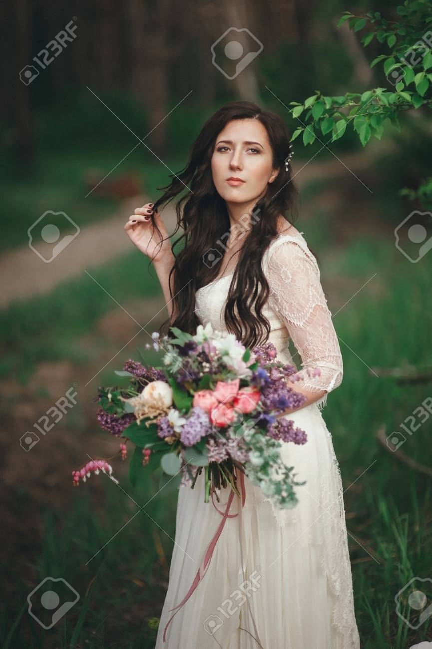 Beautiful Bride In The Forest With A Large Bouquet Of Different Stock Photo Picture And Royalty Free Image Image 72850373