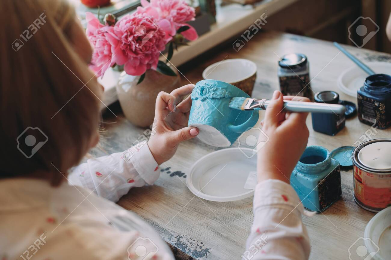 Woman working In her pottery studio. Ceramic workshop. Paint on clay cup in the pottery. Painting in pottery - 129586117