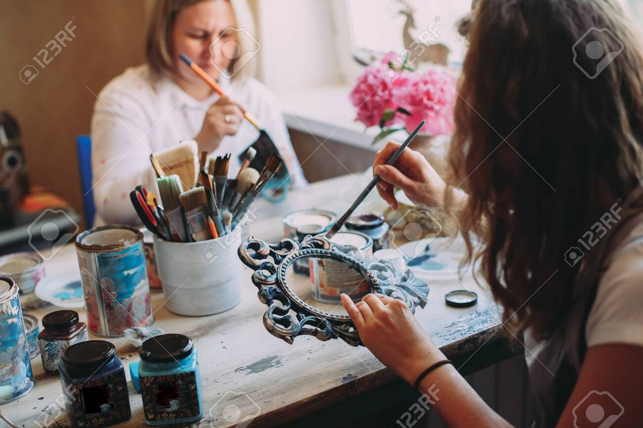 girl paints the frame with a brush. handwork. creation - 145336819