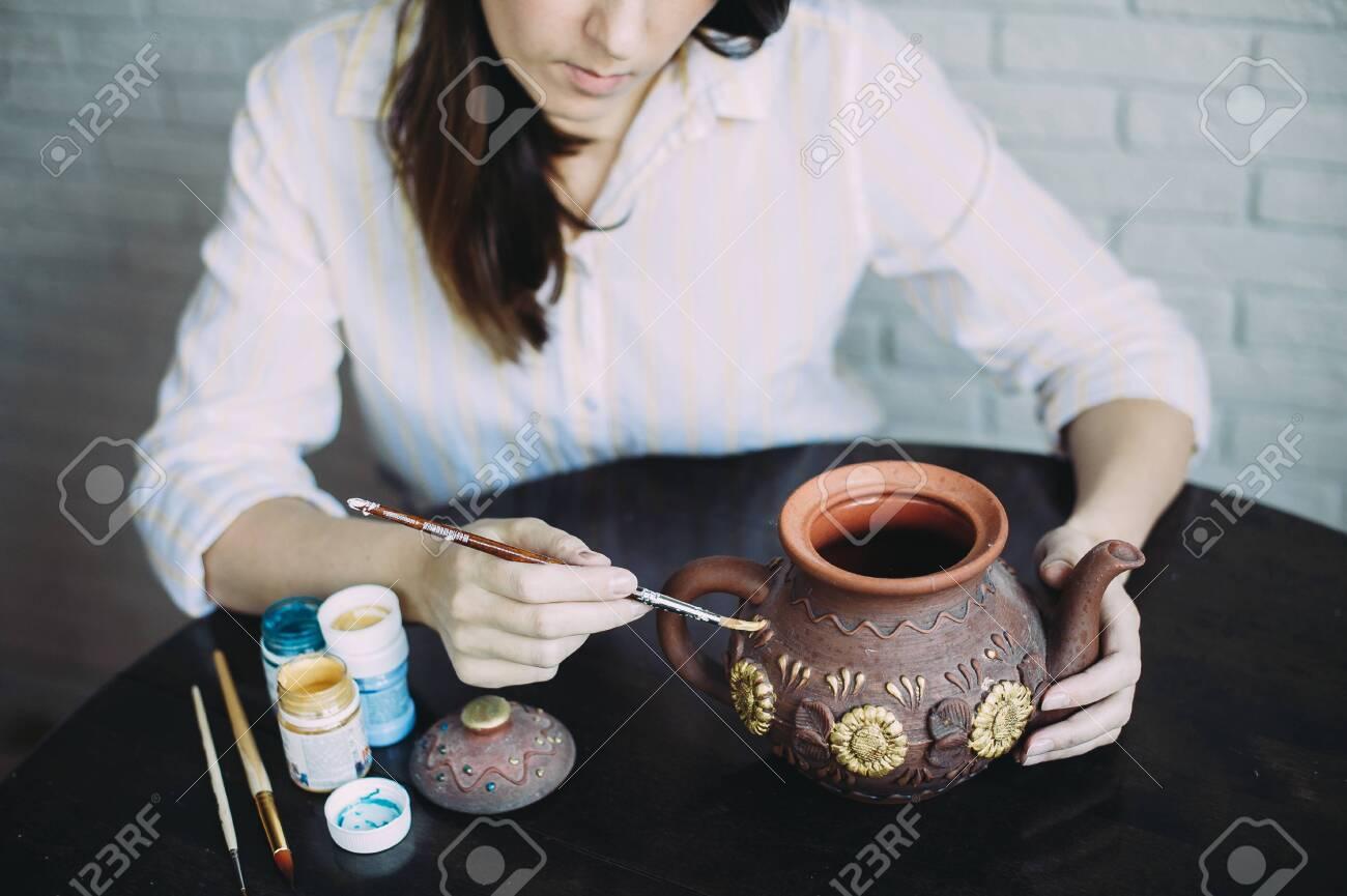 Girl artist paints a clay teapot in her workshop. Creativity. Handwork. Art. Self employment - 145846845