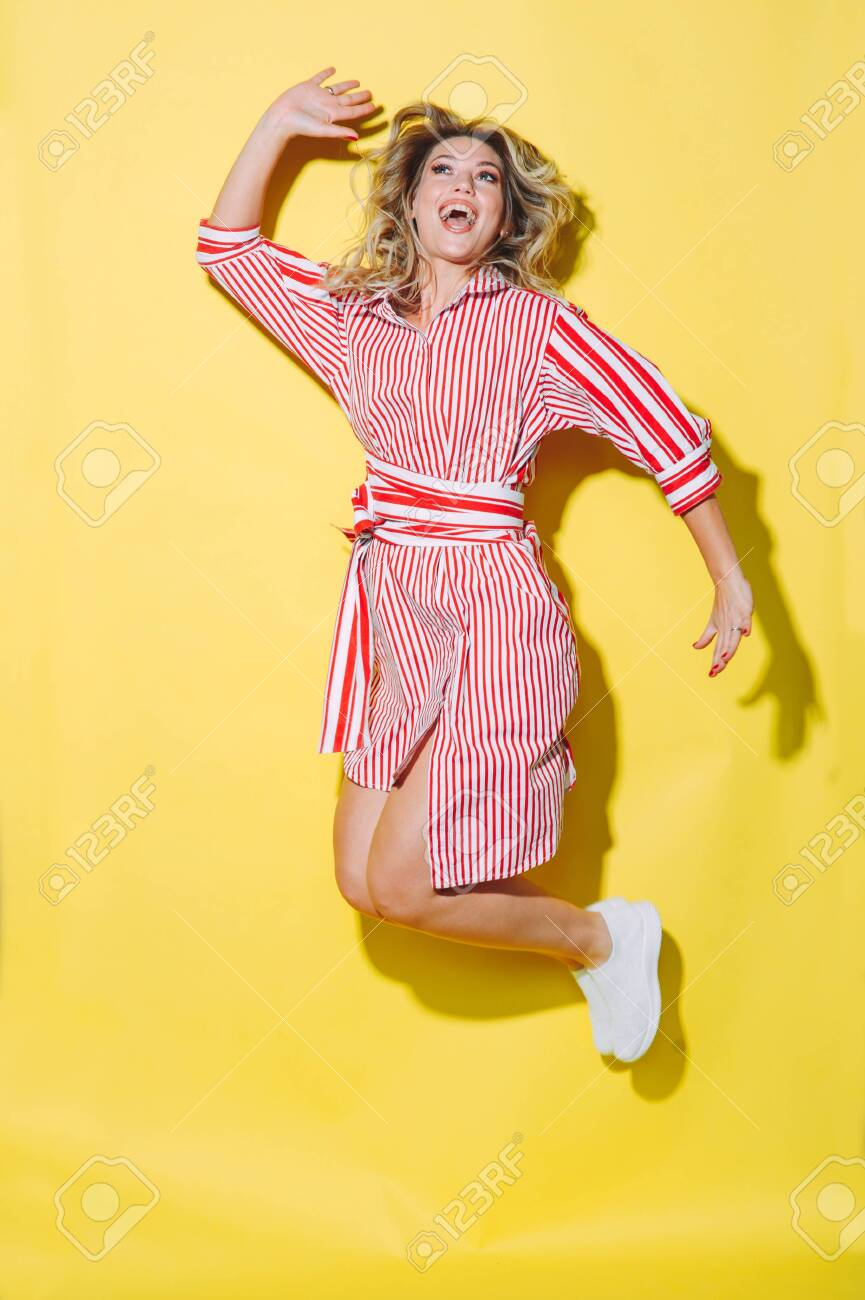 concept happy emotional young woman in red summer dress and hat jumping and laughing on yellow background - 147961494