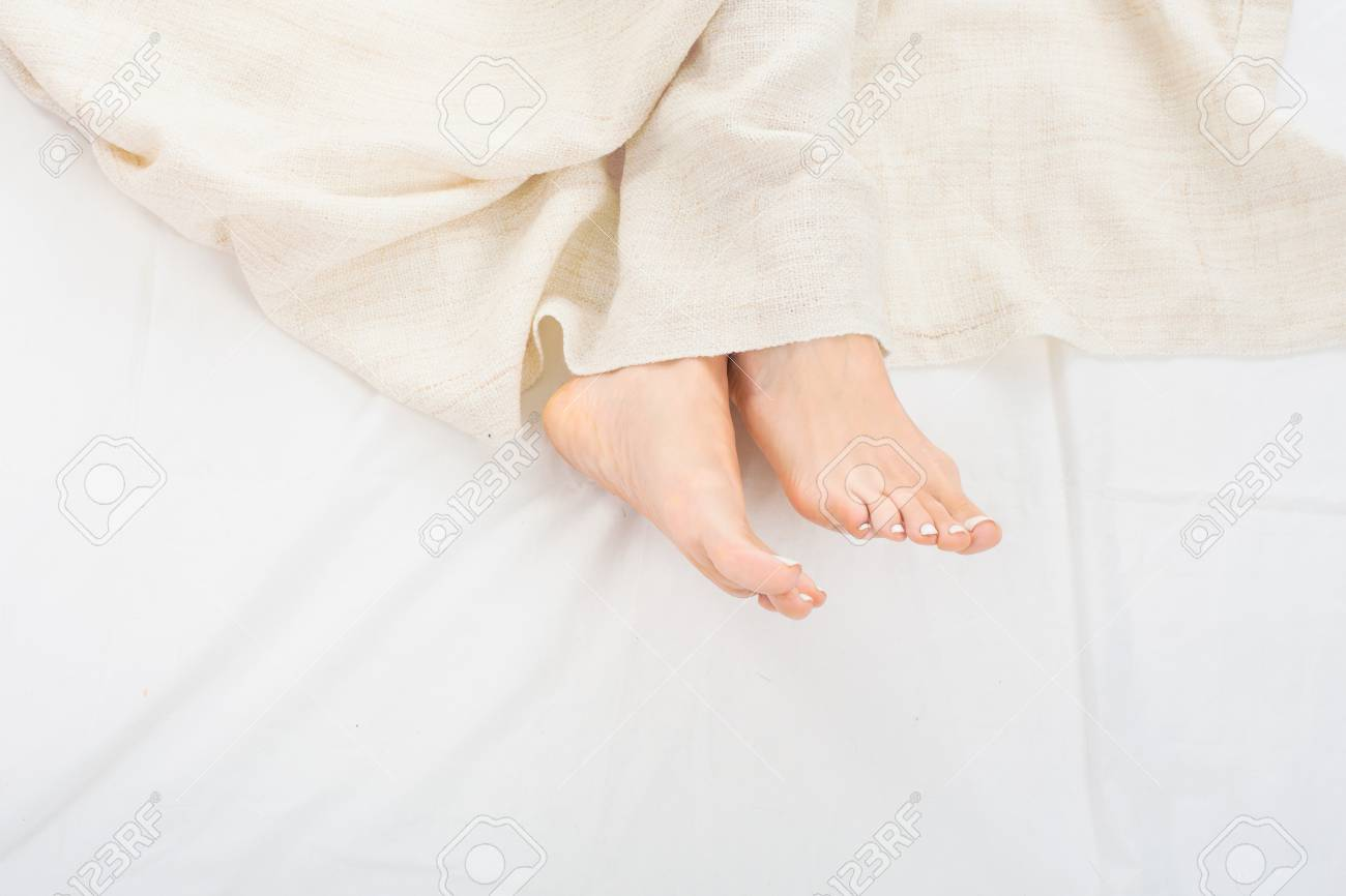b8dc6b75a2 Female feet under blanket flat lay. Female beautiful feet with red pedicure  on the bed