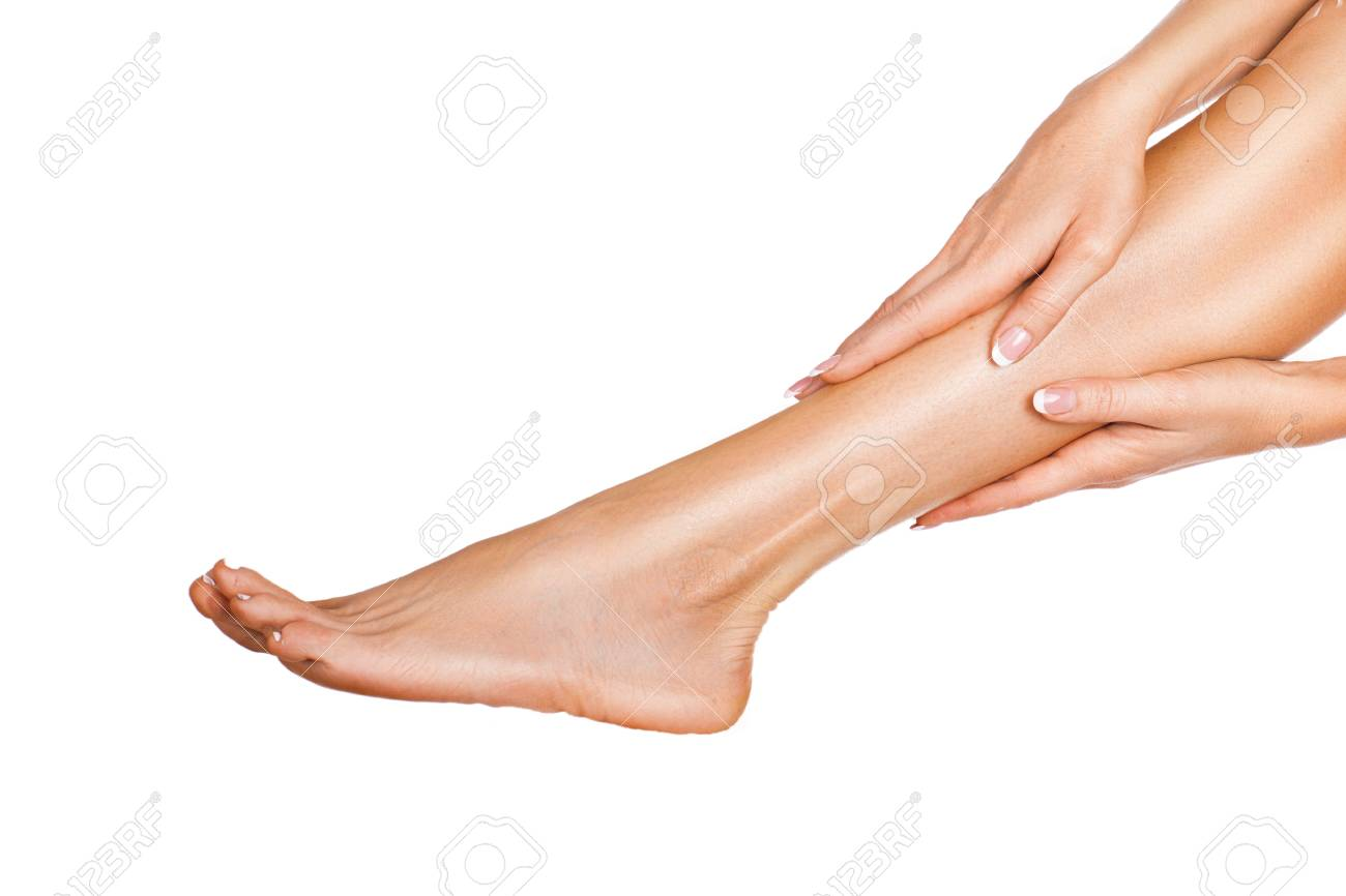 Woman massaging her legs isolated on white background. Close up view of a female legs with perfect skin and hands - 123303437