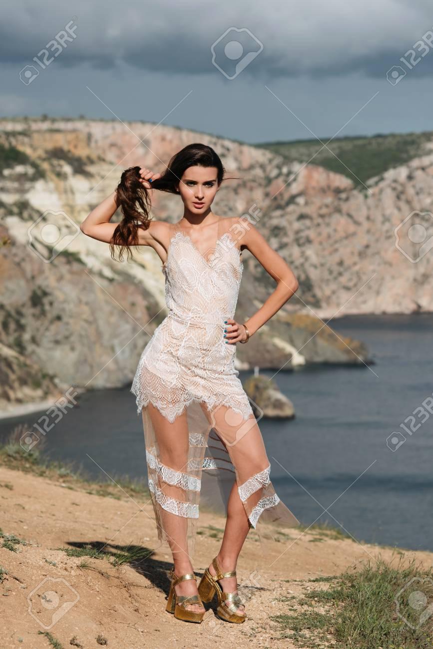 b5ece4eba264 ... vestito bianco sul mare blu profondo. Adatti il   ritratto all aperto  di bella donna sexy con le gambe esili