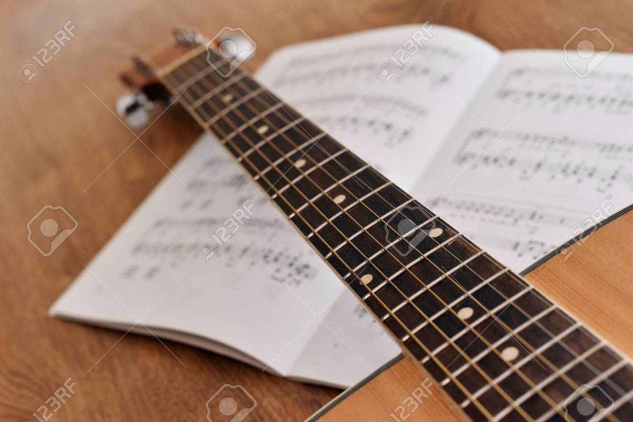 Acoustic Guitar With Notes Of Song On A Wooden Floor Guitar Stock