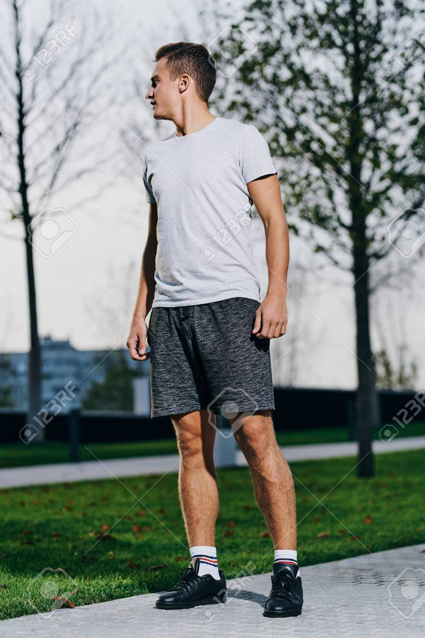 A man in shorts goes in for sports in a park in nature and a model running sneakers - 153814986