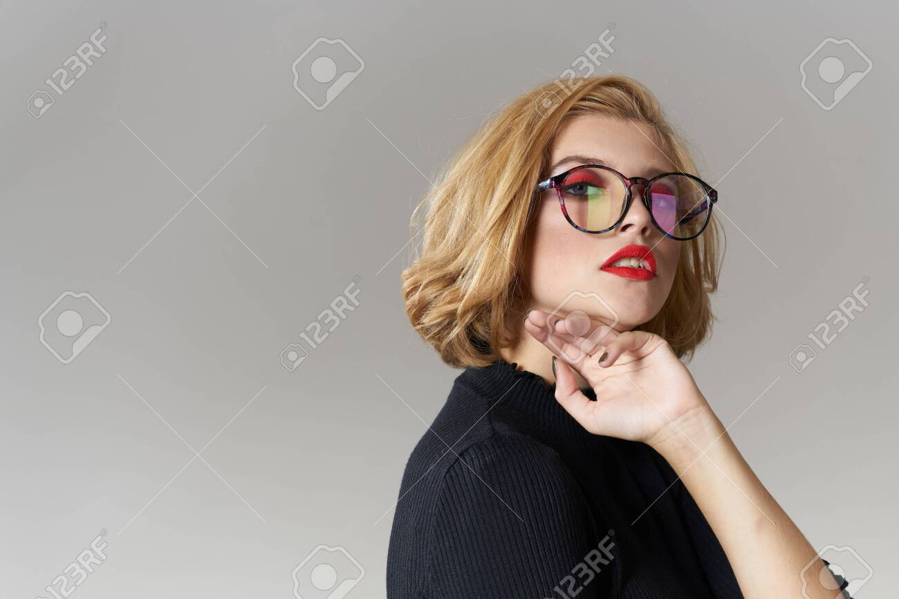 Blonde girl with glasses red lips black blouse cropped view glamor light background studio - 154155823