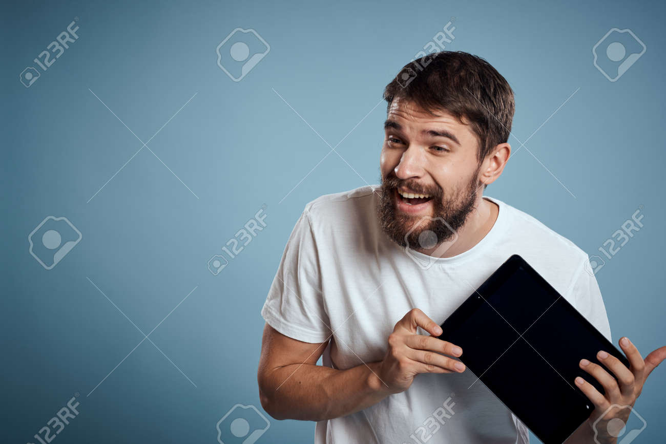 man with touch tablet in hands on blue background gesturing with hands cropped view copy space emotions model - 155723525