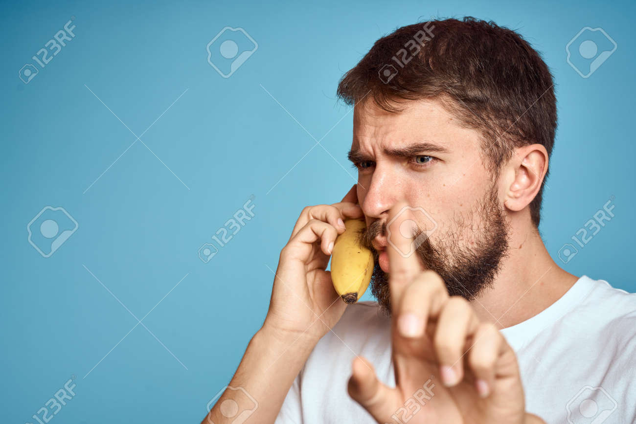 a man with a banana is caught in a white t-shirt on a blue background concept of communication by phone - 157238841