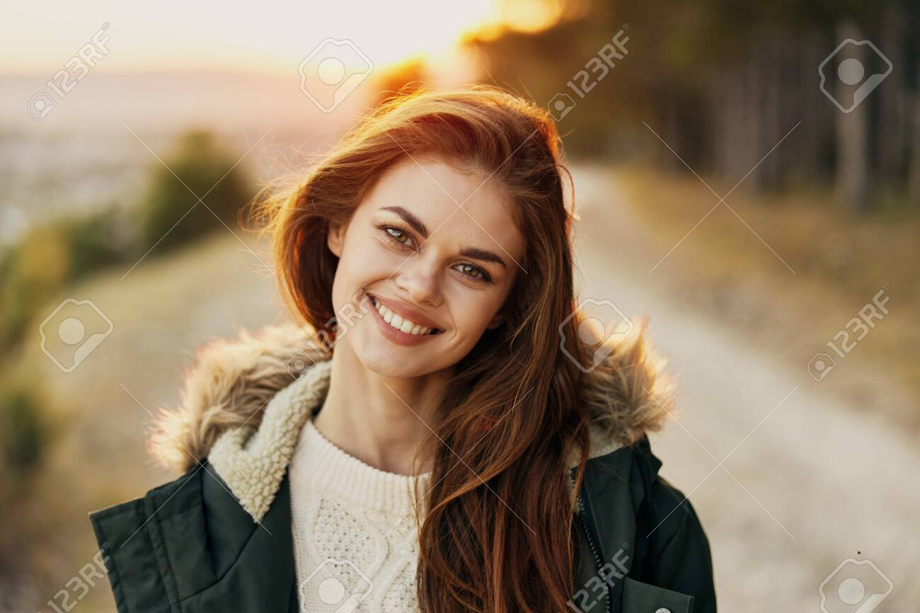 Smiling woman warm jacket Autumn forest in the background close-up - 158003248