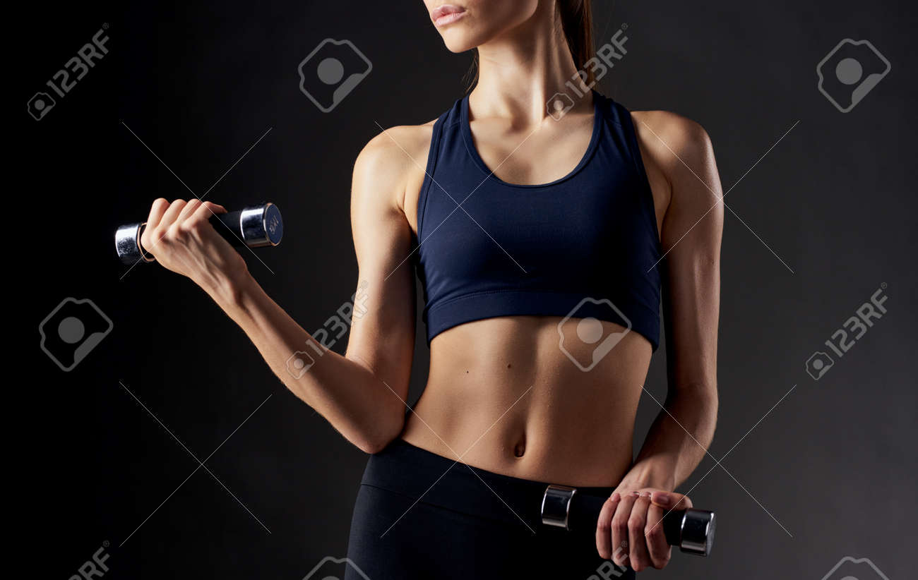 woman with pumped up abdominal muscles holds a dumbbell in her hand on a dark background - 165014774