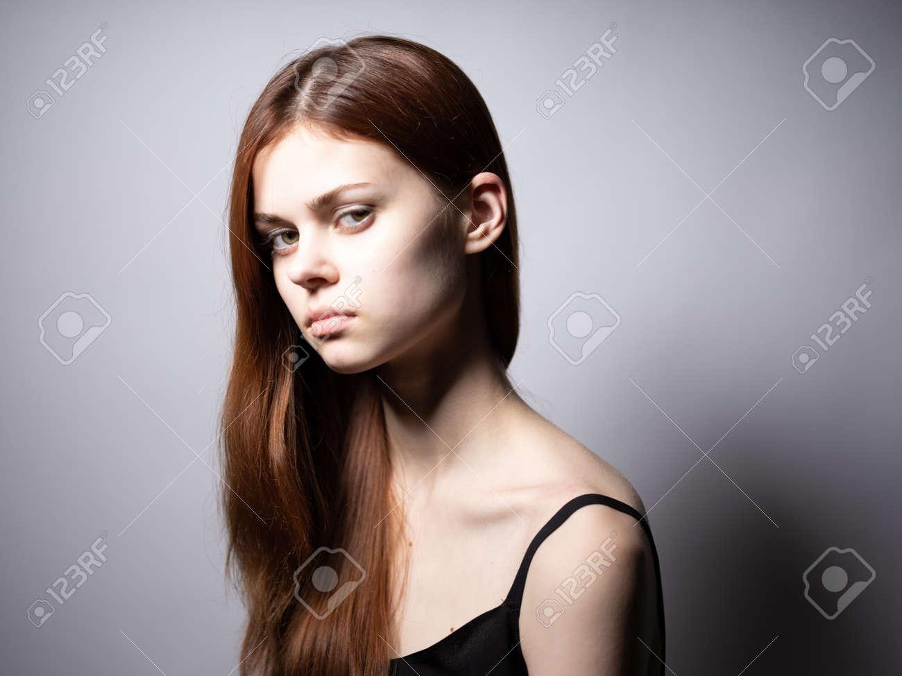 elegant lady in black t-shirt red hair sad face - 165322614