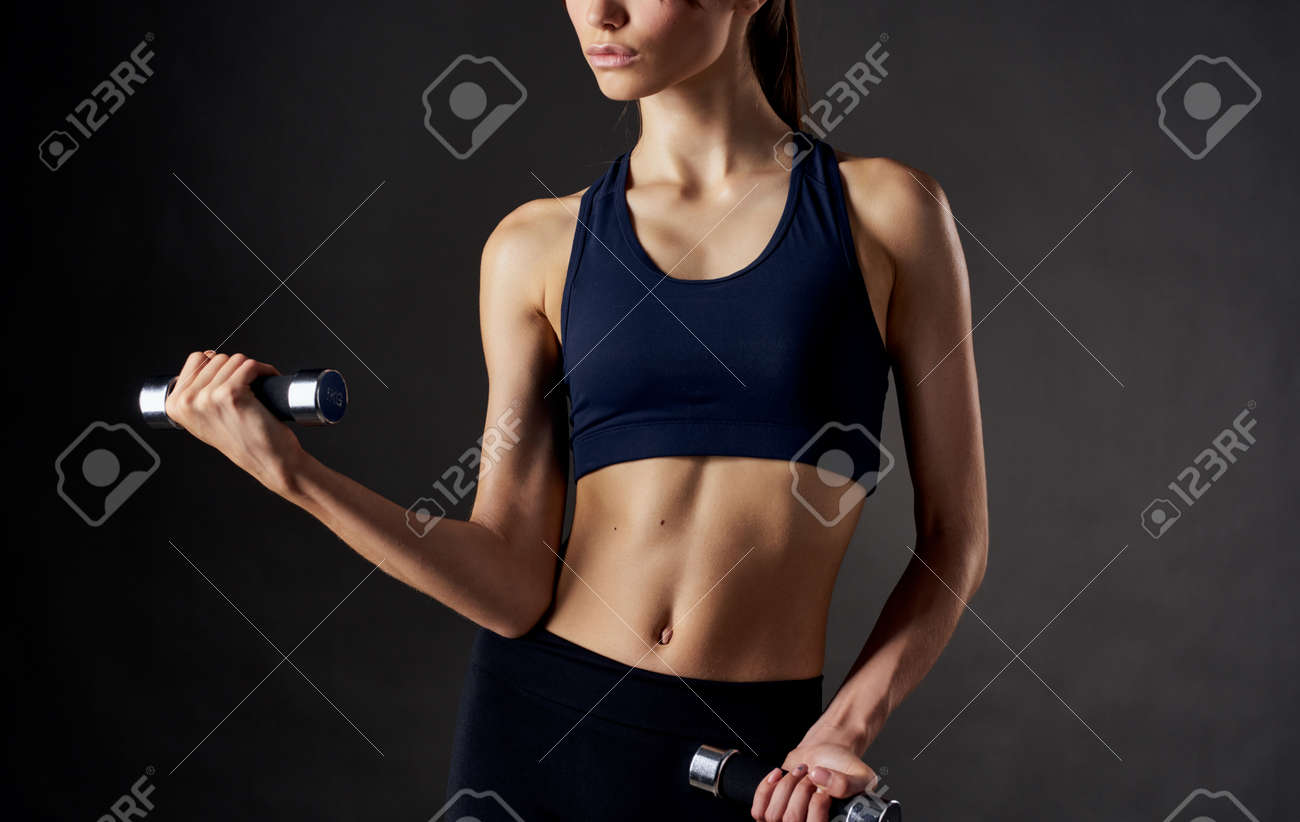 woman with muscles doing sports dumbbells in her hands and slim figure - 165457897