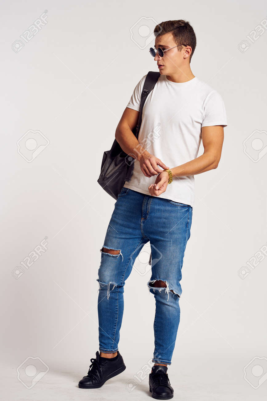 a man with a backpack on his back in jeans t-shirt full length sneakers and glasses on his face - 166360002