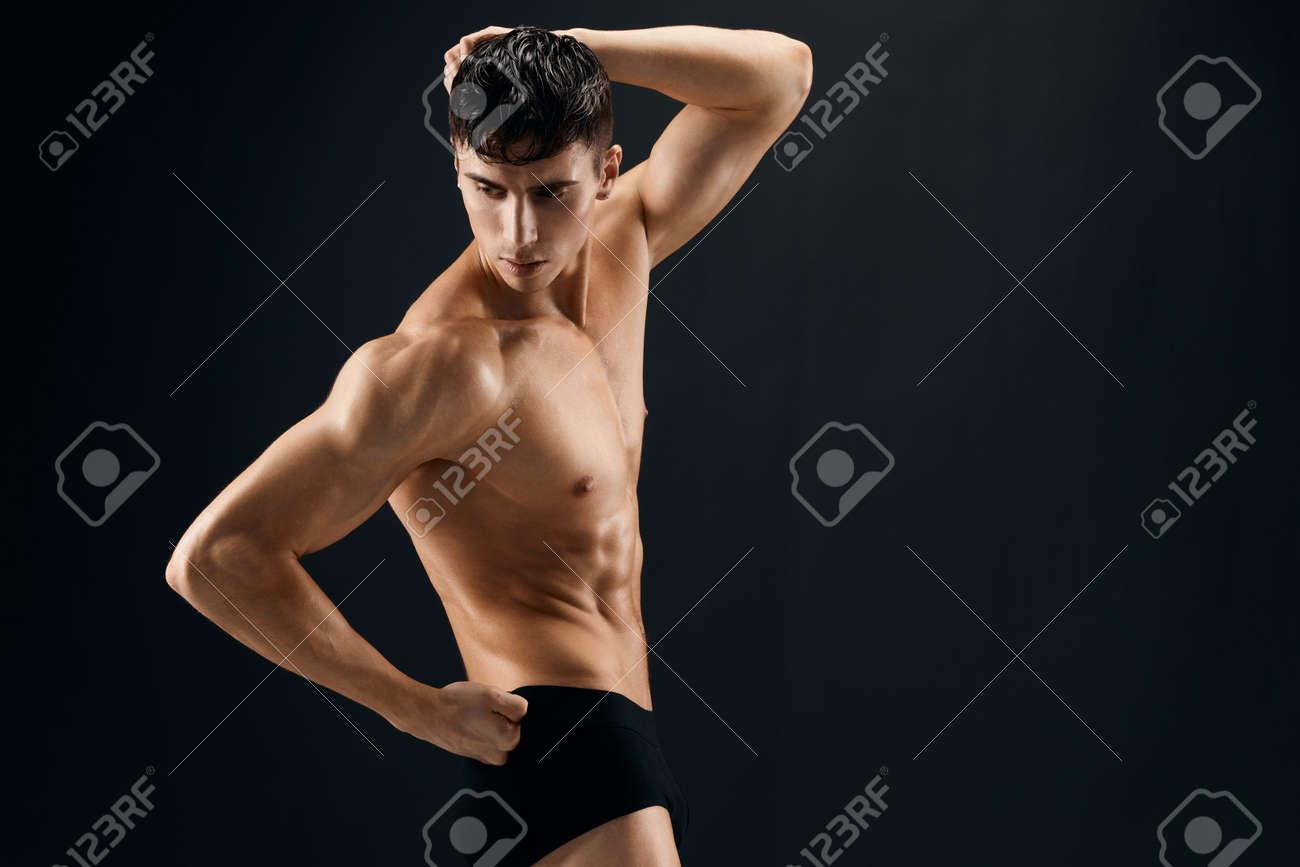 man with a pumped-up torso athlete dark background studio - 167725700