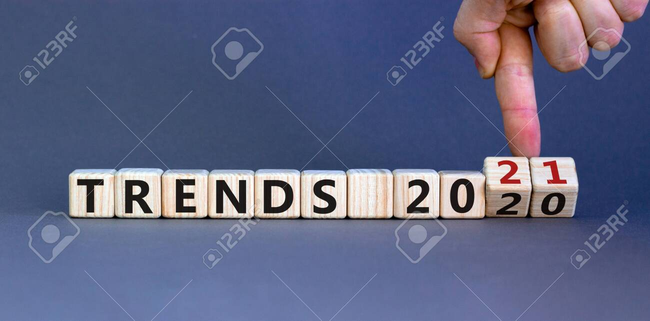 Business concept of planning 2021. Male hand flips wooden cubes and changes the inscription 'TRENDS 2020' to 'TRENDS 2021'. Beautiful gray background, copy space. - 156779110