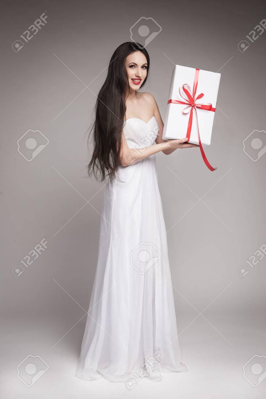 Mujer Hermosa Joven Con El Pelo Largo Y Oscuro Con Un Vestido Blanco Maxi Celebración De Regalo Envuelto En Papel Blanco Con Cinta Roja
