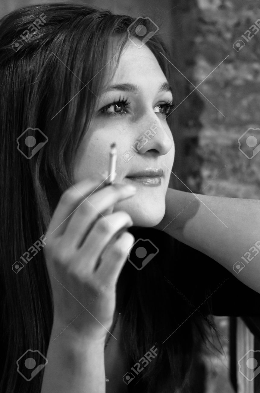 Pretty and elegant girl smoking small cigarette in black and white stock photo 12648517
