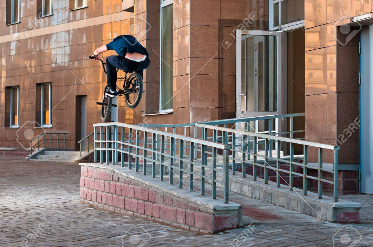 Biker doing high rail hop trick on bmx, back view Stock Photo - 13639511