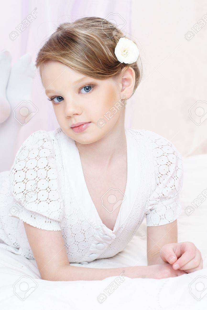 f8eaf3298a42 beautiful little girl with perfect makeup and hair-dress with flowers  lookung at you Stock