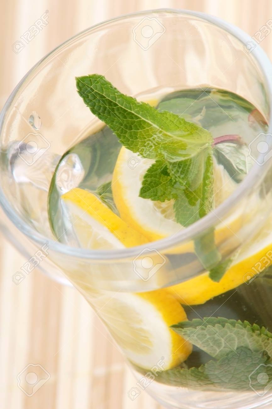 glass fresh water with mint and lemon on a bamboo table Stock Photo - 19323083