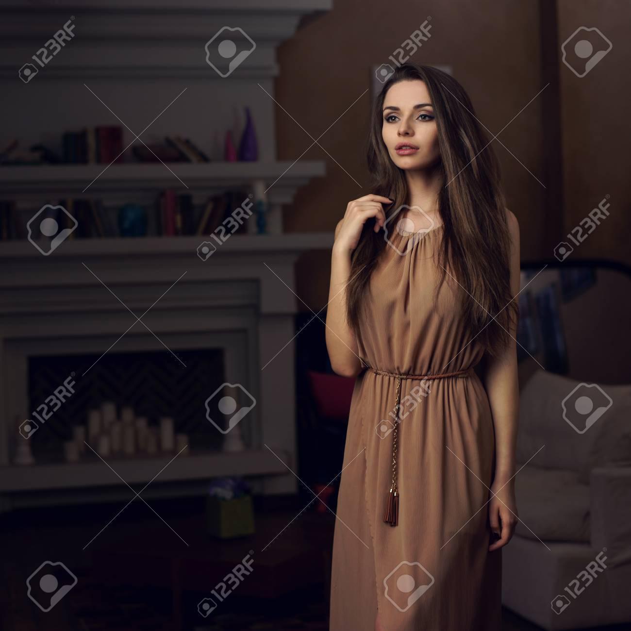 24267e073dcb8 Banque d images - Belle jeune fille debout chic et posant en brun robe de  soirée longue dans l intérieur de la maison confortable