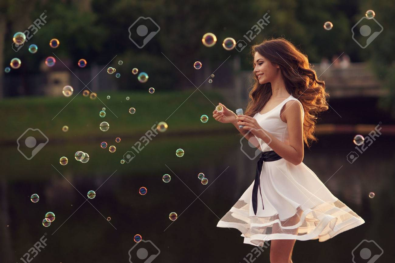 Outdoor summer portrait of young beautiful happy woman making soap bubbles in park or at nature in white dress - 55314554