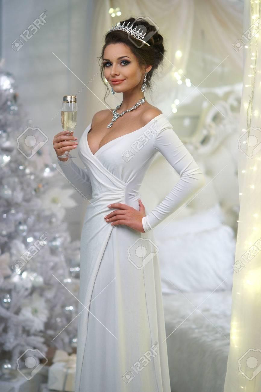 7ba644082f Foto de archivo - Joven hermosa chica en vestido de noche blanco de pie en Navidad  decorado interior con árbol de Navidad