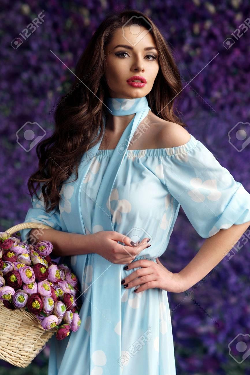 a2bdf33bdd Mujer Hermosa Joven Con La Cesta Llena De Flores De Peonía Con El Fondo  Lleno De Flores De Color Púrpura. Hermosa Niña Bonita En Vestido Azul Linda  Del ...