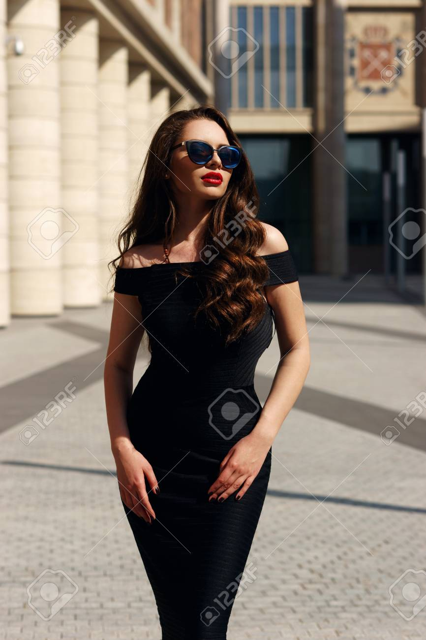 7a559d718d4 Stock Photo - Young beautiful stylish girl posing at summer city streets on  a sunny day wearing black dress and sunglasses.