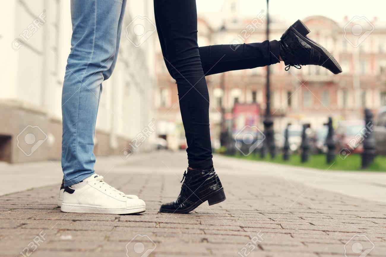 Primo piano di gambe di coppia baciare alla strada della città con pavimentazione in pietra. Uomo in jeans blu e scarpe da ginnastica bianche e donna