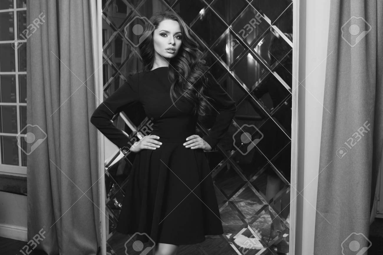 79108996-modelo-femenino-hermoso-imponente -que-lleva-el-vestido-de-cóctel-negro-colocándose-y-presentando-en-inter.jpg 01a714077f
