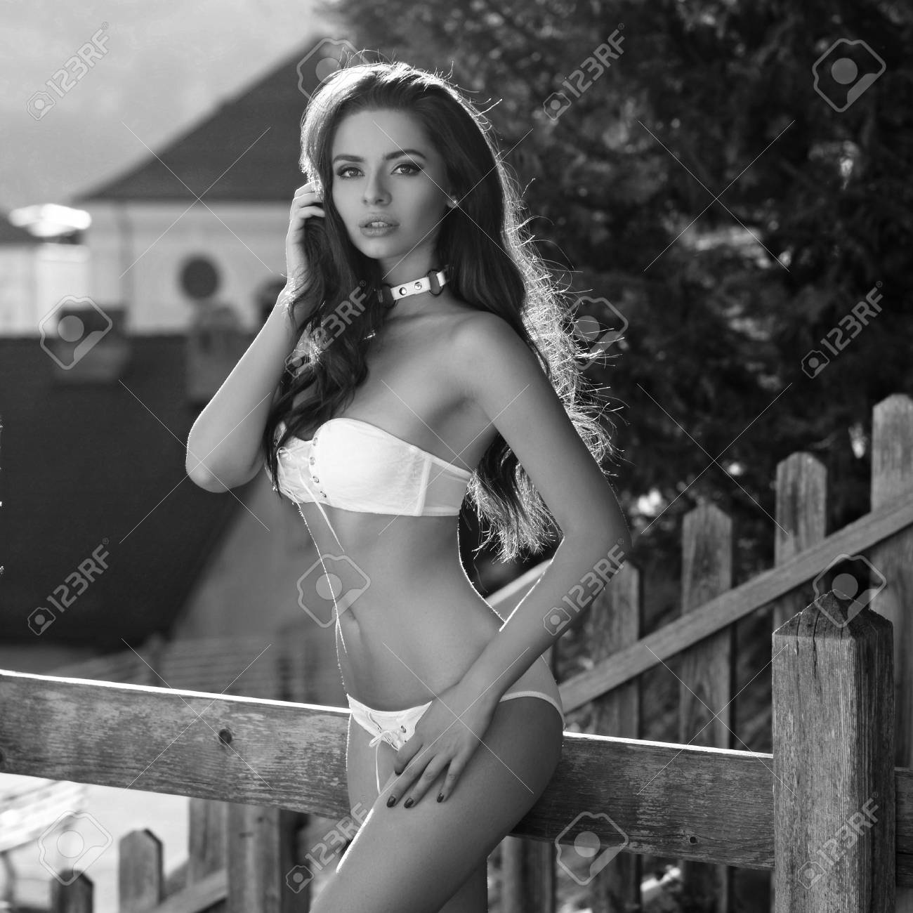 61c16cf57e Sexy and attractive young woman dressed in white bra and panties standing  against wooden fence