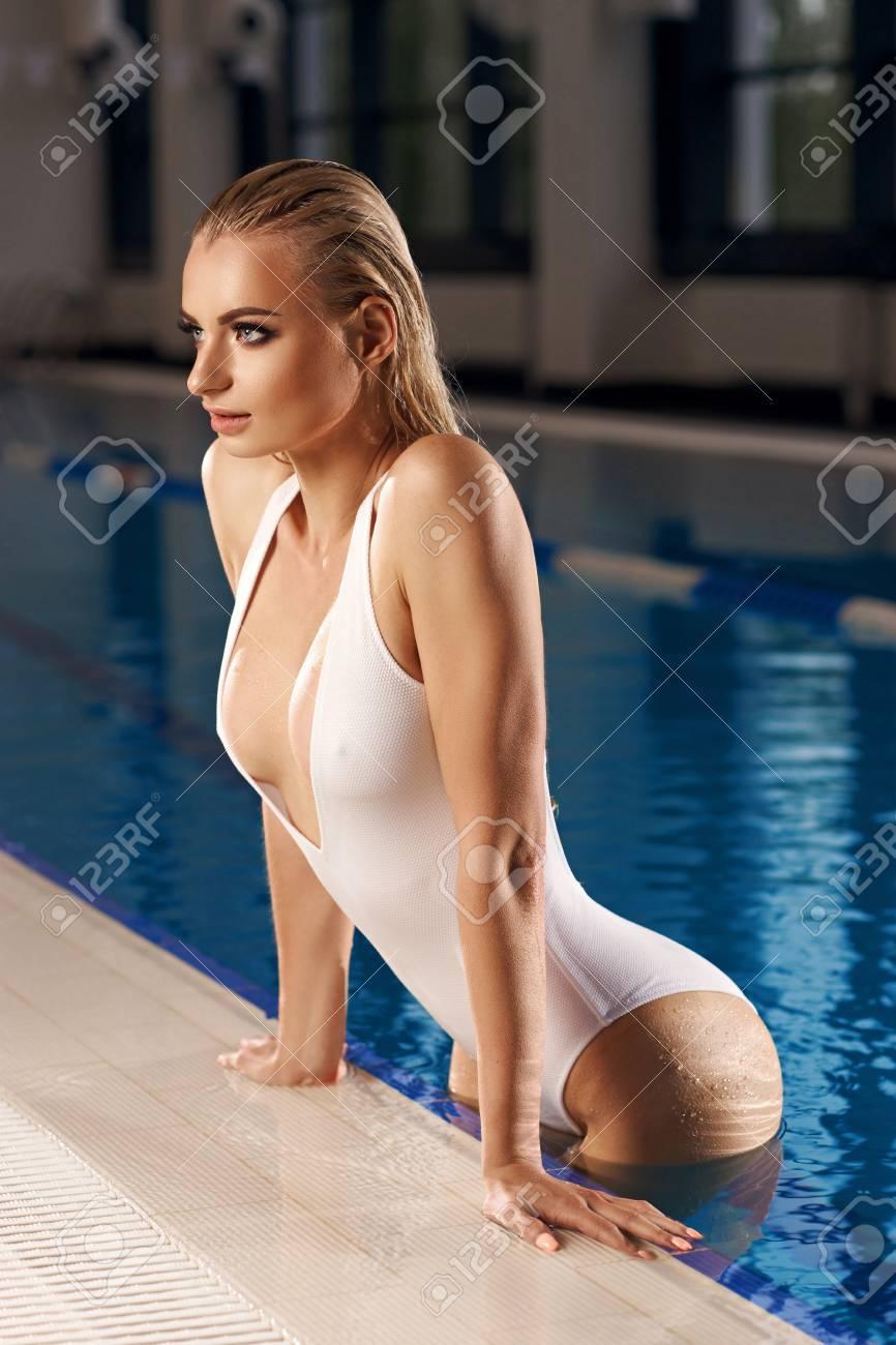 Blonde De Avec Maillot Bain Blanc Debout Vêtue Longs S'appuyant Et La Séduisante Femme Dans Cheveux Décolleté Mouillés Piscine Aux Yyfg76bv
