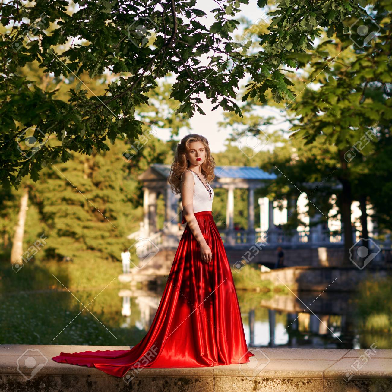 f44e29a8045 Fashion style photo of young beautiful woman in evening dress with white  top and red flying skirt posing in summer park at sunset under green trees  and ...